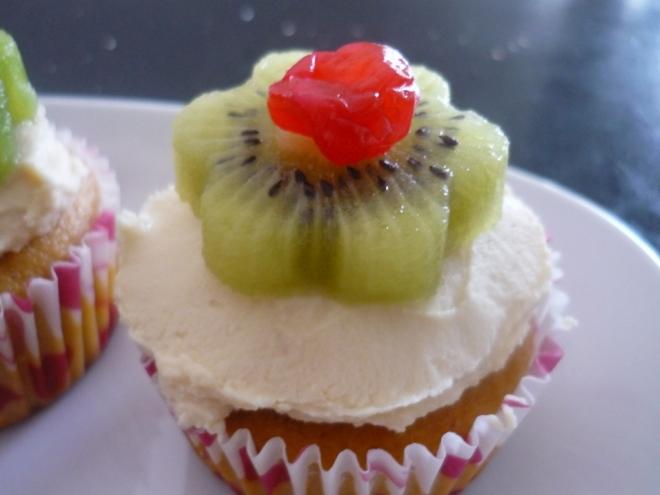 Gluten-free Vanilla Cupcake with organic coconut cream frosting, kiwi flowers and cherries.